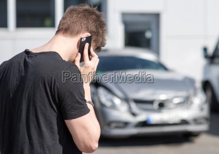 junger, mann, telefoniert, nach, einem, autounfall - 14154251