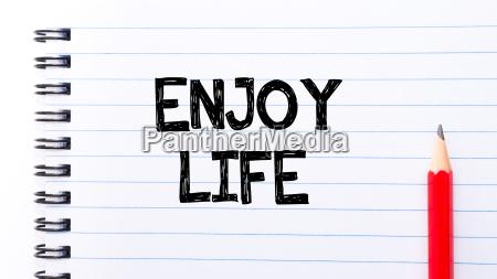 enjoy life text written on notebook