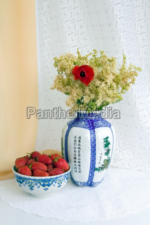 strawberries and a vase with flowers