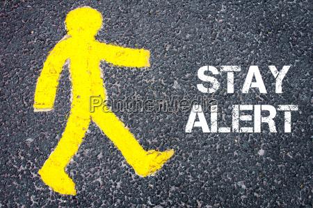 gelbe fussgaengerfigur in richtung stay alert
