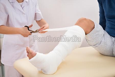 female doctor bandaging patients leg