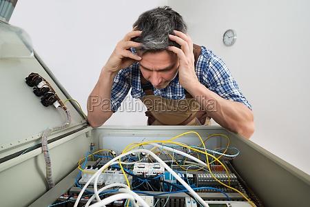 verwirrt elektriker blick in die sicherungskasten