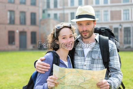 paare der jungen attraktiven touristen karte