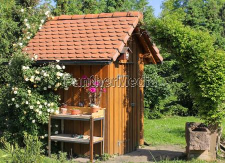 gartenhaus mit pflanztisch und brunnentrog