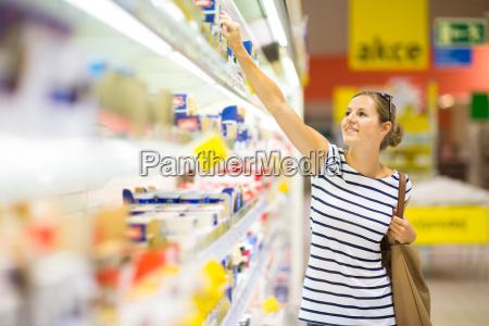 schoene junge frau shopping fuer milchprodukte