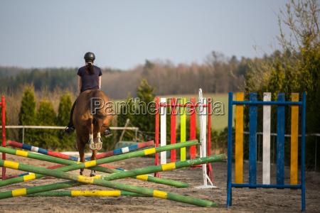junge frau springen mit pferd