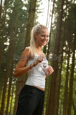 junge joggerin mit einer wasserflasche