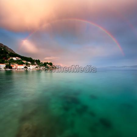 regenbogen ueber felsigem strand und kleinen