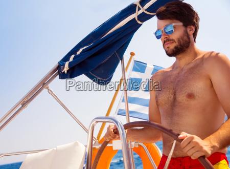 gut aussehender mann der segelboot faehrt
