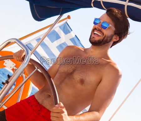 handsome man driving sailboat