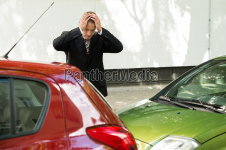 stressed driver looking at car after