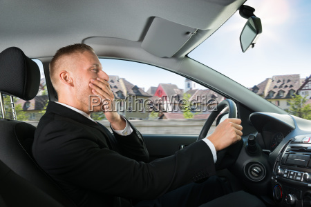 businessman yawning while driving car