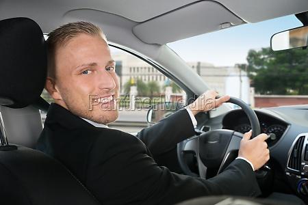 gluecklicher geschaeftsmann in seinem auto