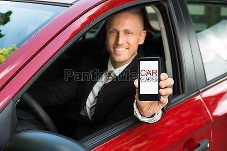 geschaeftsmann zeigt handy mit car sharing