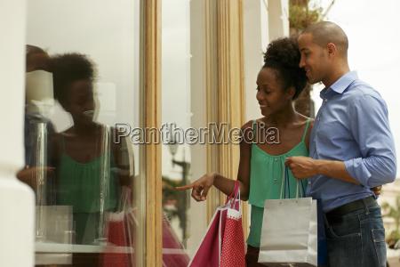 african american couple looking shop window