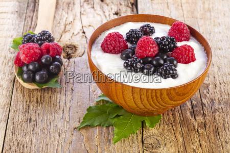 joghurt mit wilden beeren in holzschale