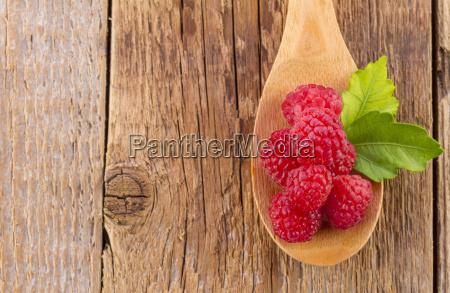 fresh raspberry in wooden spoon on