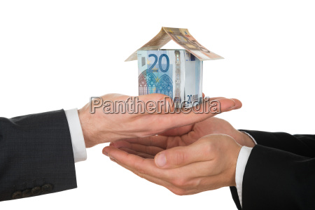 businessmans hand holding house made of