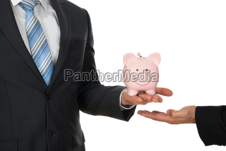 businessmans hand holding piggybank