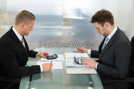two businessman using calculator at workplace