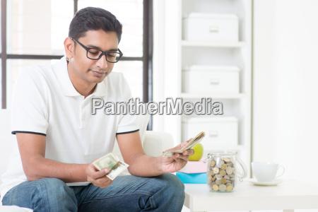 verrueckter indischer kerl der geld zaehlt