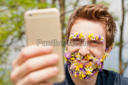 hipster mann mit blumen bedeckt texting