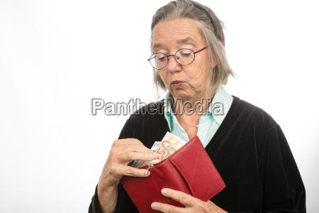 alte frau holt geld aus portemonnaie