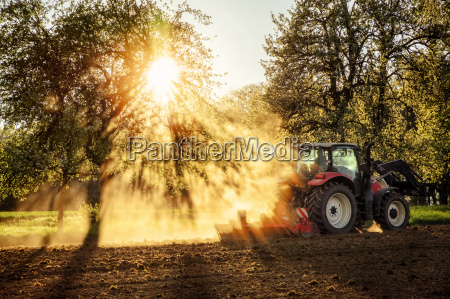 tractor ploughing a field at sunset