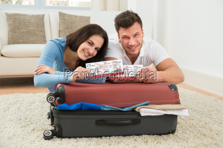 happy young couple showing boarding pass
