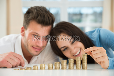 happy couple arranging stacks of golden
