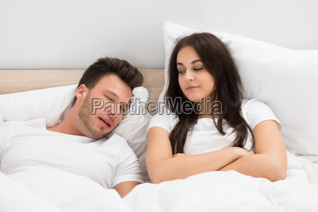 woman looking at man snoring in