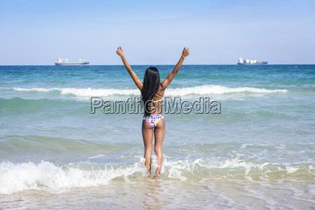 frau am strand haende hoch