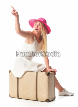 woman sitting on suitcase and pointing