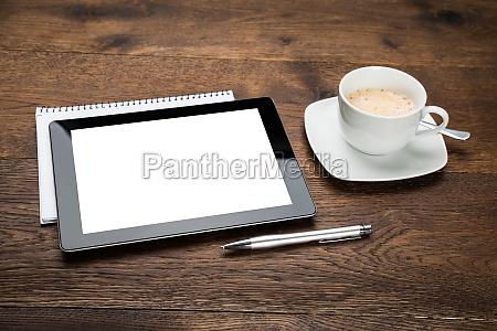 digital tablette und tagebuch mit tasse