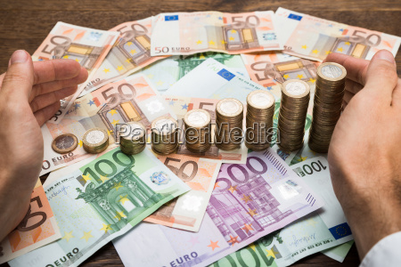 geschaeftsmann schuetzt muenzen und banknoten