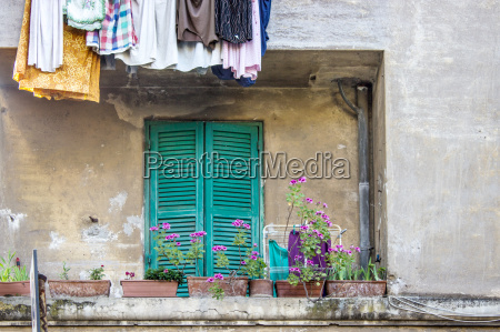 balcony with flowers and laundry on