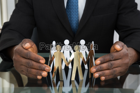 businessman protecting paper cutout people