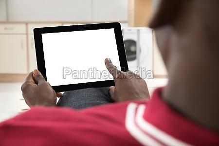 african man using digital tablet