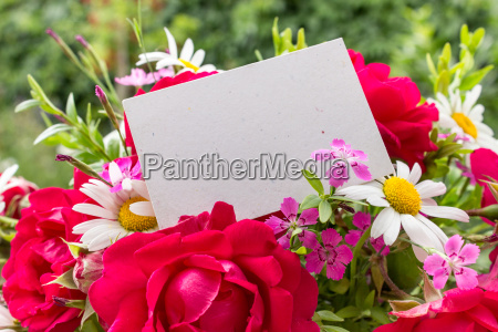 red roses and daisies and card