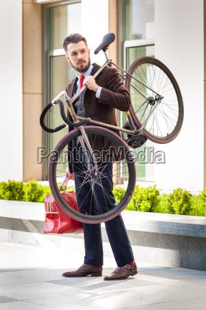 stattlicher geschaeftsmann mit seinem fahrrad in