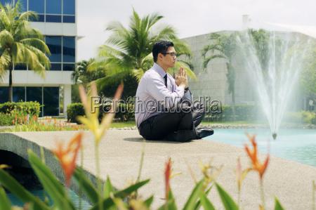 chinese business man meditate yoga outside