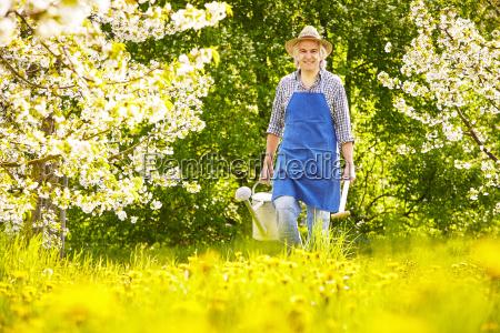 gardener watering can spade cherry tree