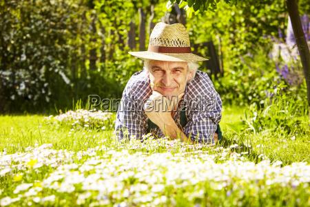 man flowering meadow hat lying