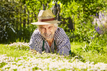 man with hat in flower meadow