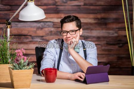 wondering female in suspenders at desk