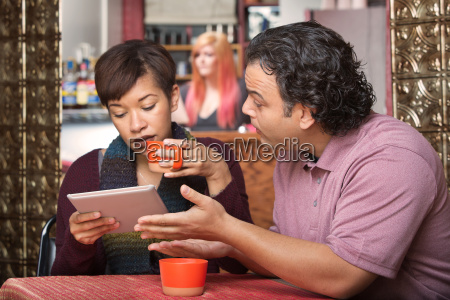 woman on tablet ignoring man