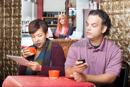 couple sneaking with digital devices