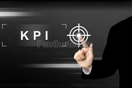 business hand pushing key performance indicator