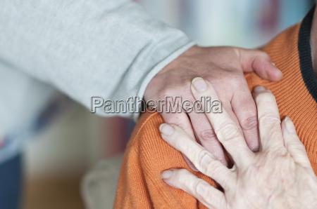 frau haelt hand auf der schulter