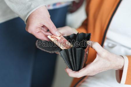 frau nimmt geld aus der geldboerse